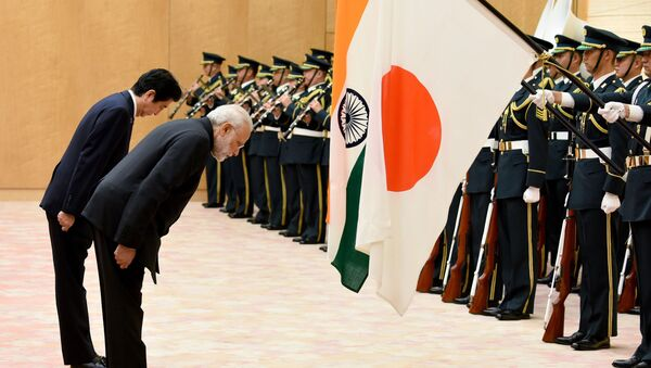 India's Prime Minister Narendra Modi (R) and his Japanese counterpart Shinzo Abe bow to national flags as they review an honor guard before their meeting at Abe's official residence in Tokyo on November 11, 2016 - Sputnik International