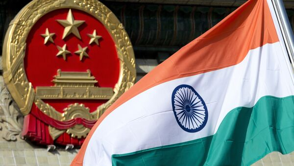 In this Oct. 23, 2013, file photo, an Indian national flag is flown next to the Chinese national emblem outside the Great Hall of the People in Beijing. China's Commerce Ministry said Thursday, Aug. 13, 2020 it has extended punitive tariffs on Indian optical fiber products for five years. The announcement follows a yearlong review after a previous tariff expired in 2019 - Sputnik International