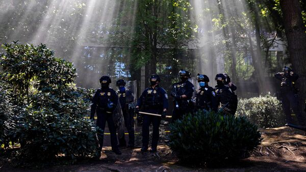 Portland Police officers observe as groups like the Proud Boys and Patriot Prayer faced off against protesters against systemic racism and police brutality in Portland, Oregon, U.S., August 22, 2020 - Sputnik International