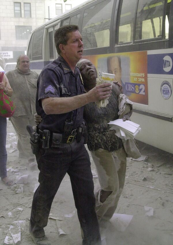 A police officer helps a woman to a bus after she fled the area near the World Trade Center towers on 11 September 2001, in New York - Sputnik International