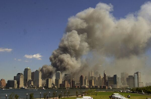 The World Trade Center is seen burning in New York City in this view from Liberty State Park in Jersey City, N.J., after the attacks on the towers and at the Pentagon in Washington - Sputnik International