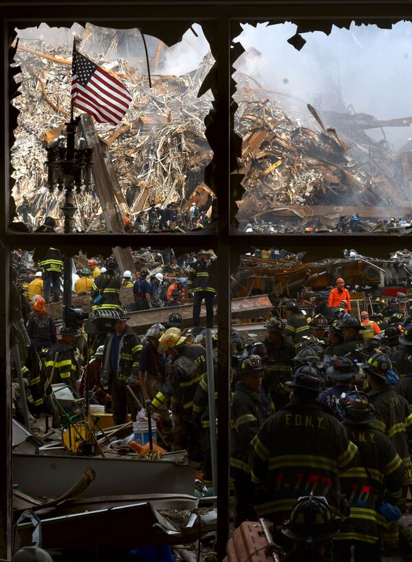 New York City firemen walk past the American flag as they work their way toward the heart of the devastation that was once the World Trade Center - Sputnik International