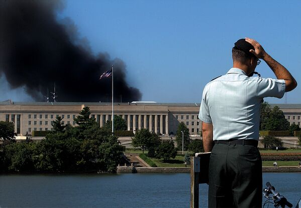 A Pentagon official outside the Pentagon, from which smoke is billowing following the 11 September 2001 attack. - Sputnik International
