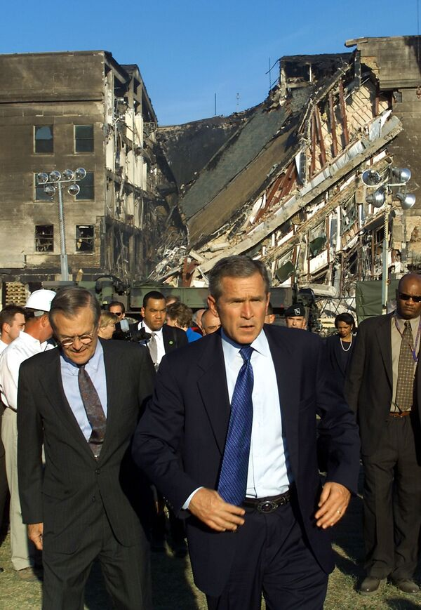 Then-US President George W. Bush (C) and then-US Secretary of Defence Donald Rumsfeld (L) tour the impact area (rear) at the Pentagon on 12 September 2001, where a hijacked airline was crashed into the building as part of a coordinated terrorist attack on the US - Sputnik International