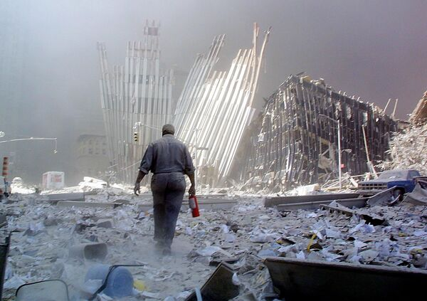 A man with a fire extinguisher walks through rubble after the collapse of the first World Trade Center Tower on 11 September 2001, in New York - Sputnik International
