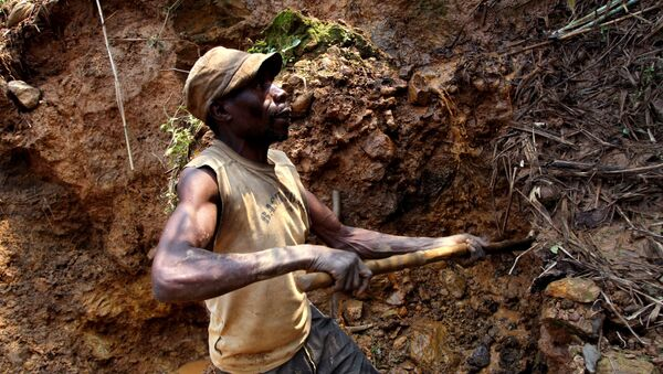 In this photo taken Aug. 17, 2012, one of the few remaining miners digs out soil which will later be filtered for traces of cassiterite, the major ore of tin, at Nyabibwe mine, in eastern Congo. Gold is now the primary source of income for armed groups in eastern Congo, and is ending up in jewelry stores across the world, according to a report published Thursday, Oct. 25, 2012, by the Enough Project. Following American legislation requiring companies to track the origin of the minerals they use, armed groups have been unable to profit from the exploitation of tin, tungsten, and tantalum, and have turned instead to gold, which is easier to smuggle across borders. Gold miners, like cassiterite miners, work in extreme conditions, with crude equipment such as pick-axes and shovels. - Sputnik International