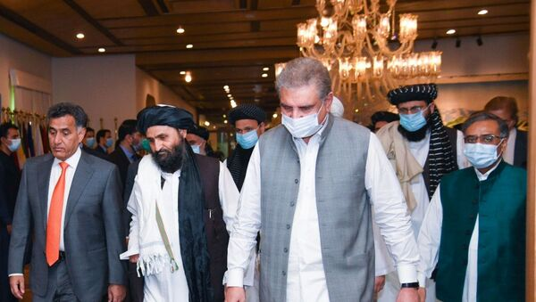 Pakistan's Foreign Minister Shah Mahmood Qureshi walks with Mullah Abdul Ghani Baradar (2nd L), the leader of the Taliban delegation, upon his arrival at the Ministry of Foreign Affairs (MOFA) office in Islamabad, Pakistan August 25, 2020.  - Sputnik International