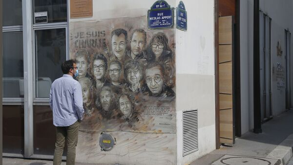A man wearing a protective face mask as a precaution against the coronavirus looks on a painting by French street artist Christian Guemy, a.k.a. 'C215' in Paris Wednesday, Sept. 2, 2020, in tribute to the members of the satirical newspaper Charlie Hebdo attack by jihadist gunmen in January 2015. Thirteen men and a woman go on trial Wednesday over the 2015 attacks against a satirical newspaper and a kosher supermarket in Paris that marked the beginning of a wave of violence by the Islamic State group in Europe. Seventeen people and all three gunmen died during the three days of attacks in January 2015 - Sputnik International