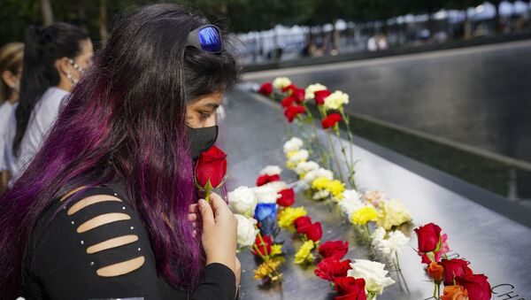 A mourner kisses a rose through her face mask before placing it in a name cut-out of the deceased at the National September 11 Memorial and Museum, Friday, Sept. 11, 2020, in New York - Sputnik International