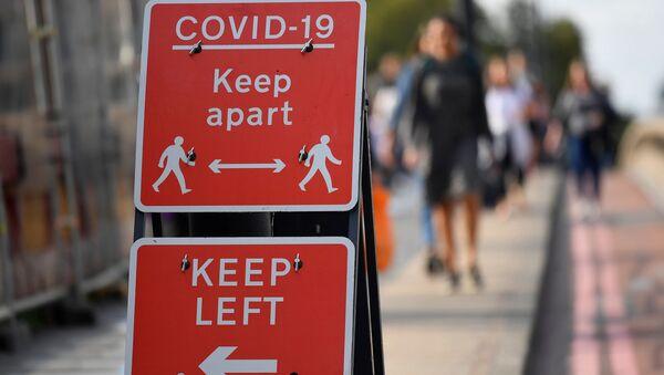 Pedestrians walk near public health signs - Sputnik International