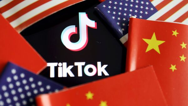 China and U.S. flags are seen near a TikTok logo in this illustration picture taken July 16, 2020. REUTERS/Florence Lo/Illustration - Sputnik International
