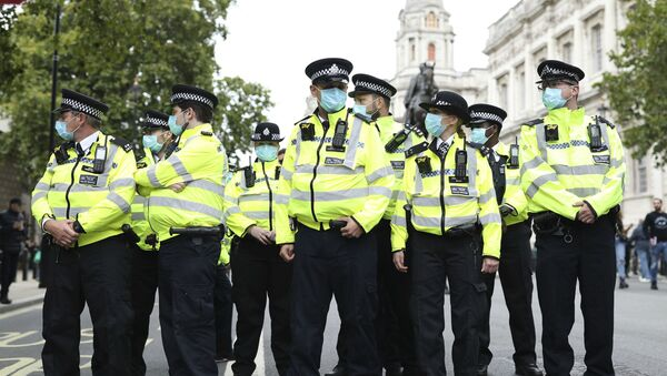 Police officers wearing face masks stand guard during a protest opposed to COVID-19 pandemic restrictions, in Trafalgar Square, London, 29 August, 2020 - Sputnik International