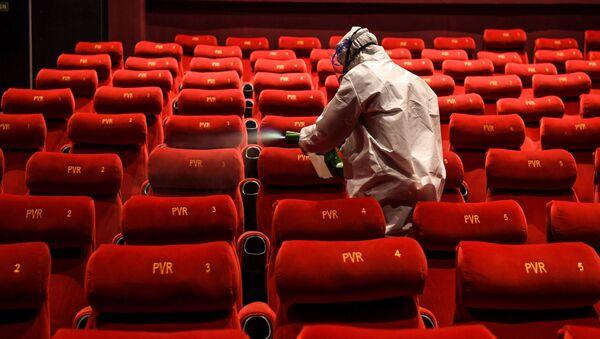 A worker wearing a PPE suit sanitises a cinema - Sputnik International