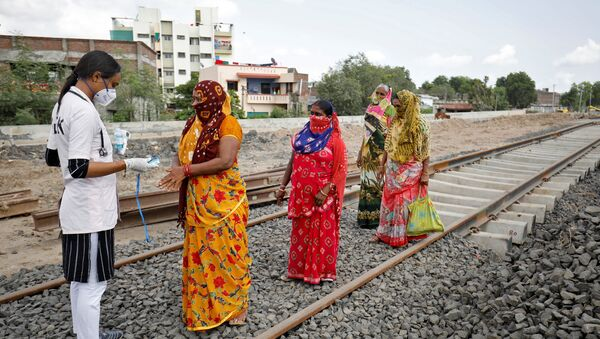 A healthcare worker puts a pulse oximeter on a woman's finger to check her oxygen level during survey for the coronavirus disease (COVID-19) at the construction site of a railway track, amidst the spread of the disease in Babla village on the outskirts of Ahmedabad, India, 15 September 2020 - Sputnik International