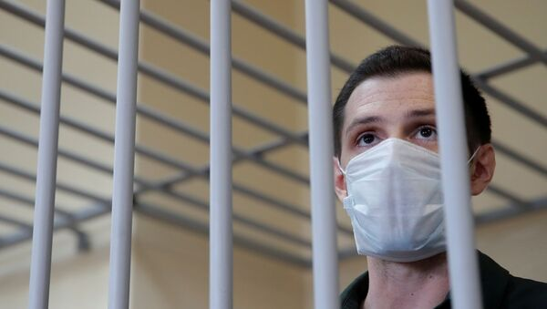 Former U.S. Marine Trevor Reed, who was detained in 2019 and accused of assaulting police officers, stands inside a defendants' cage during a court hearing in Moscow, Russia July 30, 2020. - Sputnik International