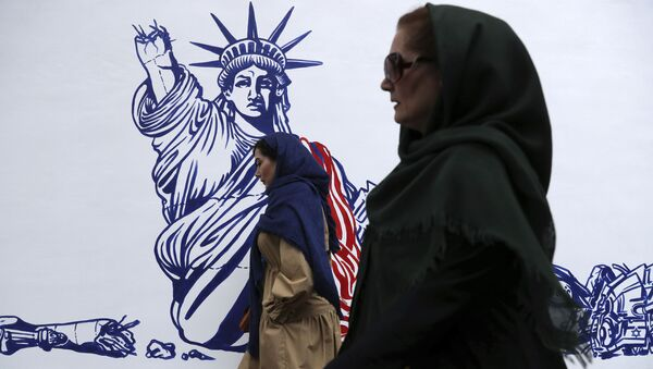 People walk past a satirical drawing of Statue of Liberty after new anti-U.S. murals on the walls of former U.S. embassy unveiled in a ceremony in Tehran, Iran, Saturday, Nov. 2, 2019 - Sputnik International