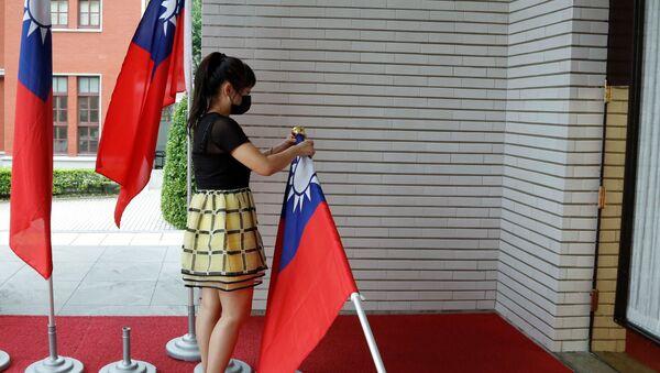 A staff member collects Taiwan flags outside of the Legislative Yuan in Taipei, Taiwan September 1 - Sputnik International