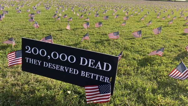 A sign near the Washington Monument reads, 200,000 dead. They deserved better. Each flag in the installation represents 10 Americans who died of COVID-19. - Sputnik International