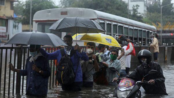People wade through a waterlogged road after heavy rainfall in Mumbai, India, September 23 2020. - Sputnik International