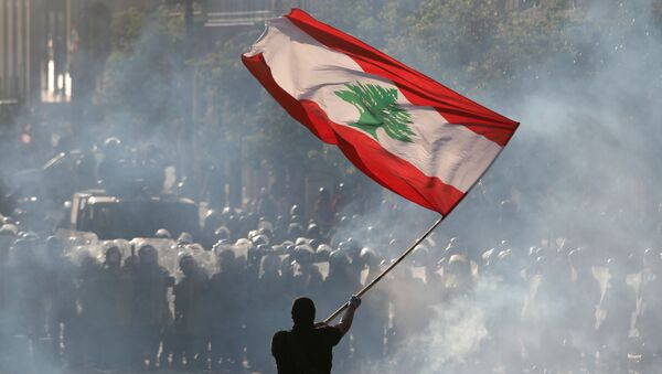 A demonstrator waves the Lebanese flag in front of riot police - Sputnik International