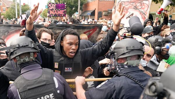 A protester clashes with police after a grand jury considering the March killing of Breonna Taylor, a Black medical worker, in her home in Louisville, Kentucky, voted to indict one of three white police officers for wanton endangerment, in Louisville, Kentucky, U.S. September 23, 2020. - Sputnik International