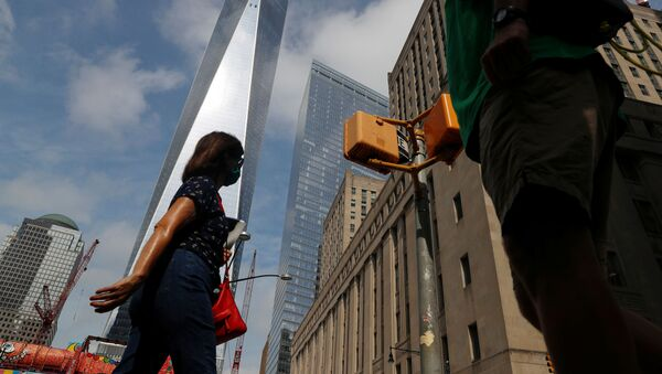 People wearing protective face masks walk by One World Trade Center two days before the 19th anniversary of the 9/11 attacks, amid the coronavirus disease (COVID-19) pandemic, in the lower section Manhattan, New York City, U.S., September 9, 2020.  - Sputnik International