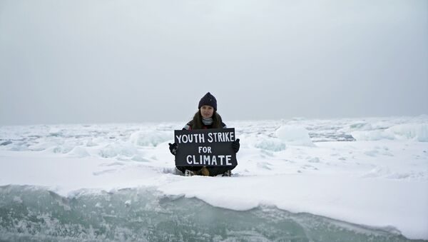 Environmental activist and campaigner Mya-Rose Craig, 18, holds a cardboard sign reading youth strike for climate as she sits on the ice floe in the middle of the Arctic Ocean, hundreds of miles above the Arctic Circle, 20 September 2020. - Sputnik International