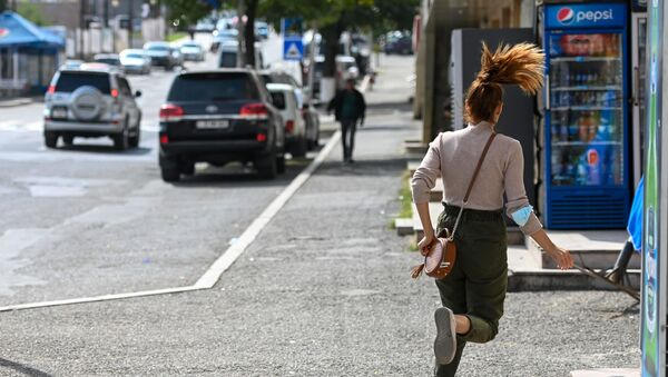 A young woman runs down a street in Stepanakert - Sputnik International