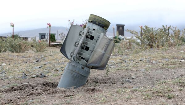 The remains of a rocket shell are seen near a graveyard in the town of Ivanyan (Khojaly) in the breakaway region of Nagorno-Karabakh, October 1, 2020 - Sputnik International