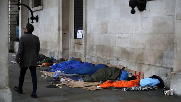 A man walks past homeless people sleeping rough in London - Sputnik International