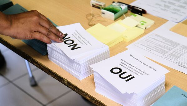 A person picks up a voting form as he prepares to cast his vote at a polling station in the referendum on independence on the French South Pacific territory of New Caledonia in Noumea on October 4, 2020 - Sputnik International