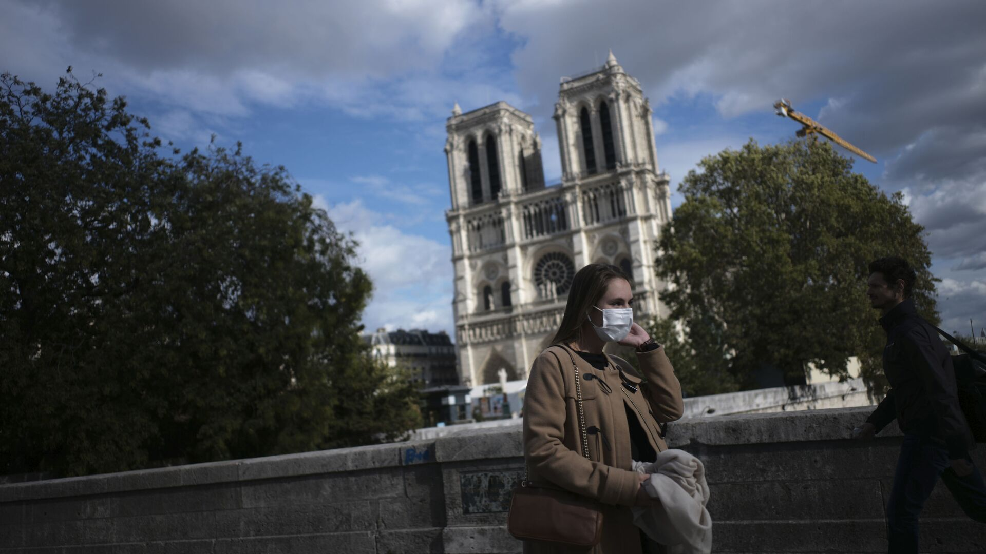 A woman walks by Notre Dame cathedral Saturday Sept.26, 2020 in Paris. While France suffered testing shortages early in the pandemic, ramped-up testing since this summer has helped authorities track a rising tide of infections across the country. - Sputnik International, 1920, 18.09.2021