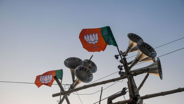 A worker ties a Bharatiya Janata Party (BJP) flag on a structure bearing loudspeakers to prepare for the next day the political rally of Home Minister Amit Shah, in Kolkata on February 29, 2020. - Sputnik International