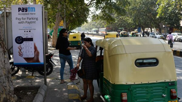In this photograph taken on February 27, 2017, Indian pedestrians walk past a sign advertising Indian electronic and cellphone-based payment system Paytm outside a parking area in New Delhi - Sputnik International