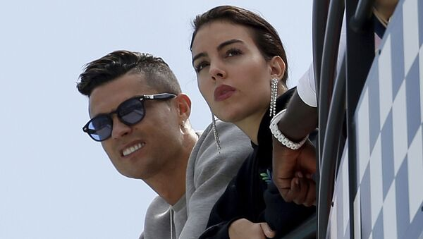 In this 23 May 2019, file photo, Cristiano Ronaldo, left, is flanked by his partner Georgina Rodriguez as they watch the second practice session for a Formula One race at the Monaco racetrack, in Monaco. - Sputnik International