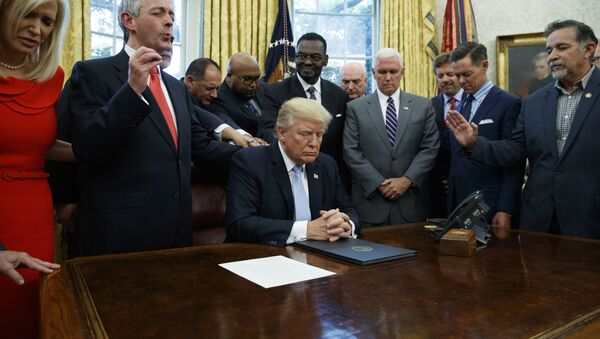 In this Sept. 1, 2017 file photo, religious leaders pray with President Donald Trump after he signed a proclamation for a national day of prayer to occur on Sunday, Sept. 3, 2017, in the Oval Office of the White House in Washington. - Sputnik International