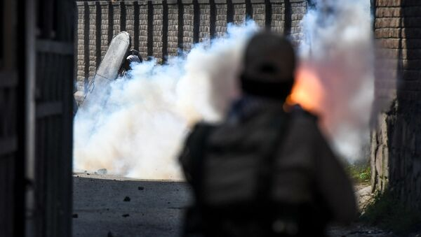 A security personnel (R) fires tear gas towards protesters during clashes with government forces in Batamaloo area of Srinagar on September 17, 2020.  - Sputnik International