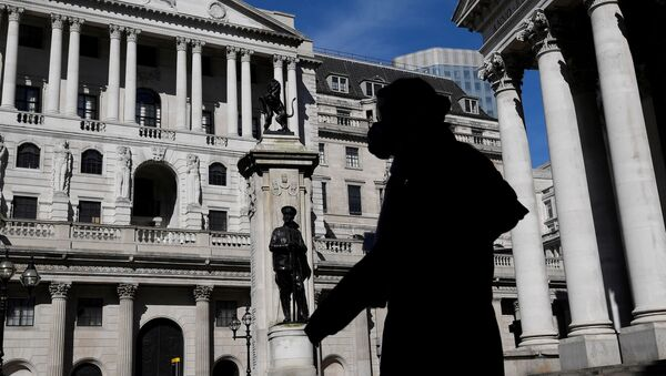 A person wearing a mask walks past the Bank of England in London, Britain, March 23, 2020 - Sputnik International