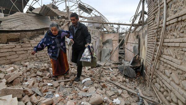 A man helps an elderly woman to walk out of a damaged house carrying her belongings following the recent shelling by Armenian forces, in Ganja, Azerbaijan.  - Sputnik International
