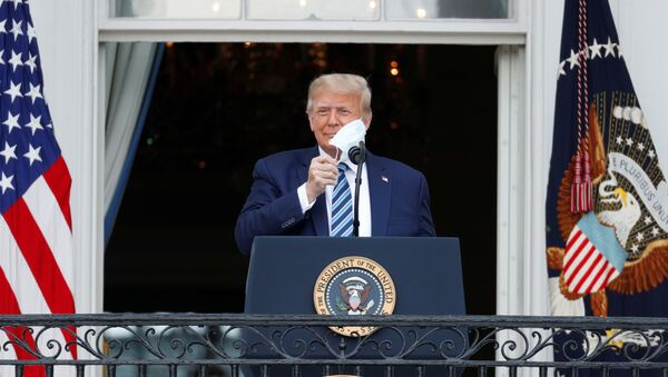 U.S. President Donald Trump takes off his face mask as he comes out on a White House balcony to speak to supporters gathered on the South Lawn for a campaign rally that the White House is calling a peaceful protest in Washington, U.S., October 10, 2020. REUTERS/Tom Brenner - Sputnik International