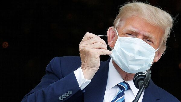 U.S. President Donald Trump, with bandages seen on his hand, takes off his face mask as he comes out on a White House balcony to speak to supporters gathered on the South Lawn for a campaign rally that the White House is calling a peaceful protest in Washington, U.S., October 10, 2020. - Sputnik International