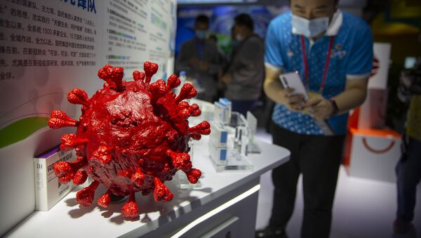 A visitor wearing a face mask takes a photo of a model of a coronavirus and boxes for COVID-19 vaccines at a display by Chinese pharmaceutical firm Sinopharm at the China International Fair for Trade in Services (CIFTIS) in Beijing, Saturday, Sept. 5, 2020. With the COVID-19 pandemic largely under control, China's capital on Saturday kicked off one of the first large-scale public events since the start of the coronavirus outbreak, as tens of thousands of attendees were expected to visit displays from nearly 2,000 Chinese and foreign companies showcasing their products and services. - Sputnik International