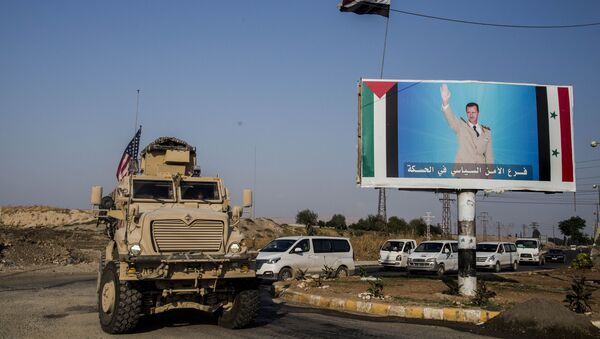 FILE - In this Saturday, Oct. 26. 2019 file photo, a U.S. military vehicle drives south of the northeastern city of Qamishli, likely heading to the oil-rich Deir el-Zour area where there are oil fields, or possibly to another base nearby, as it passes by a poster showing Syrain President Bashar Assad. - Sputnik International