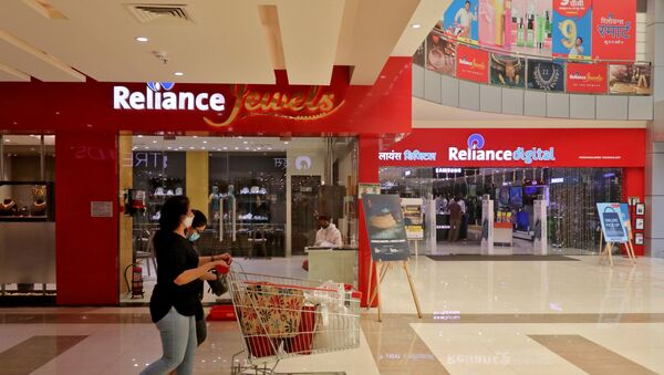 A customer wearing a protective mask pushes a trolley with grocery items past Reliance Jewels and Reliance Digital stores in Mumbai, India. - Sputnik International