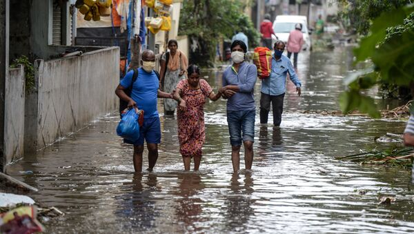 Residents carrying their belongings help a woman (C) while making their way on a flooded street following heavy rains in Hyderabad on October 14, 2020.  - Sputnik International