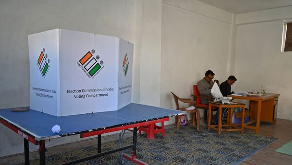 Election officials sit inside an empty polling station during the fifth phase of India's general elections in Kashmir's Shopian district, south of Srinagar, on May 6, 2019 - Sputnik International