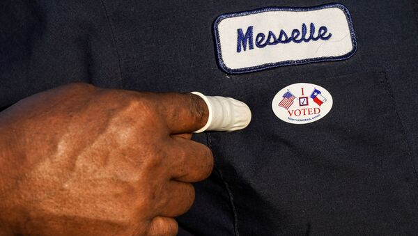 A person wearing a finger sack points at an I Voted sticker after casting ballot for the upcoming presidential election as early voting begins in Houston, Texas, U.S., October 13, 2020. - Sputnik International
