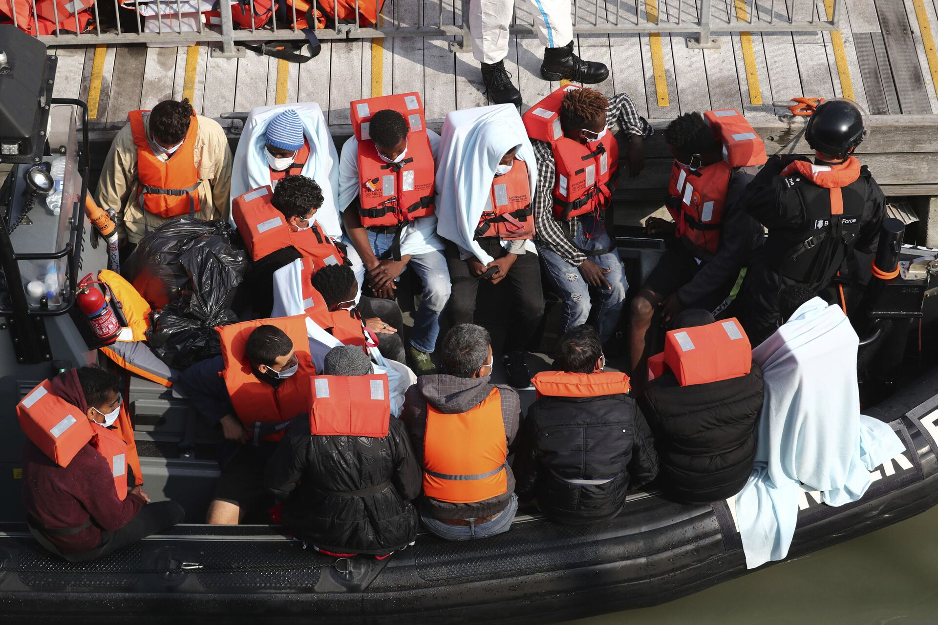 A group of people, thought to be migrants wait on a Border Force rib to come ashore at Dover marina in Kent, England after a small boat incident in the English Channel, Tuesday Sept. 22, 2020.  - Sputnik International, 1920, 07.09.2021