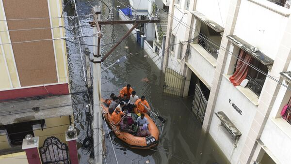 National Disaster Response Force (NDRF) personnel evacuate local residents in a boat along a flooded street following heavy rains in Hyderabad on October 15, 2020. - Sputnik International