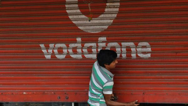 A staff opens the shutter of a shop depicting an advertisement of the telecom company Vodafone in Mumbai on February 21, 2020 - Sputnik International
